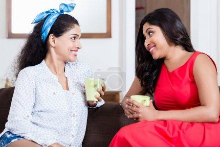 Deux amies à boire thé ou café à l'intérieur