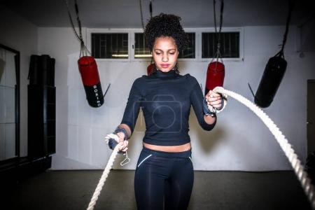 Young fit woman exercising with battle ropes during functional training