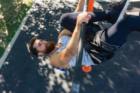 Photo for High-angle view of a strong and determined young man doing hanging oblique leg raises for abdominal muscles during street workout - Royalty Free Image
