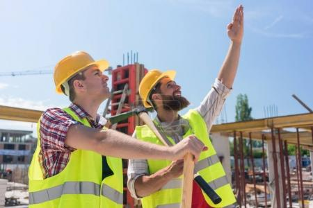Determined young worker pointing up while imagining the height of a building