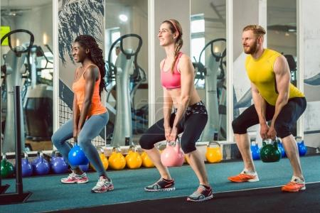 Three young people holding kettlebells during functional training