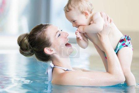 Photo pour Mère heureuse et son nouveau-né en classe de natation pour nourrissons - image libre de droit