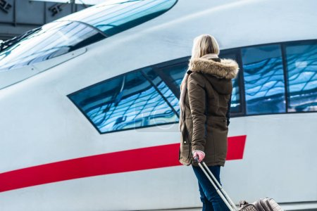 Femme attendant son train avec bagages en gare prêt à voyager