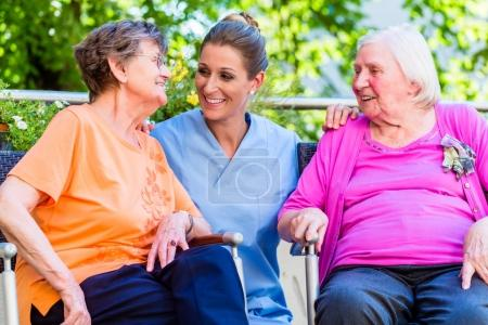 Geriatric nurse having chat with senior women in retirement home
