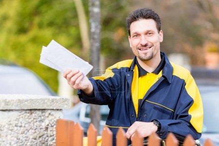 Foto de Cartero entregar cartas al buzón de un destinatario - Imagen libre de derechos