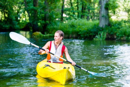 Photo for Woman paddling with canoe on forest river in summer - Royalty Free Image