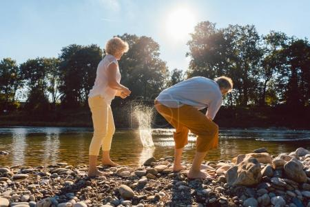 Full length rear view of two barefoot senior people enjoying retirement and simplicity while throwing stones into river in sunny day