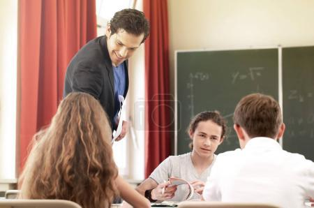 Teacher standing while math lesson in front of blackboard and teach pupils in school
