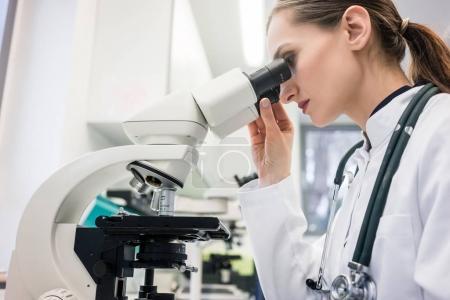 Doctor or biologist scrutinizing tissue under microscope