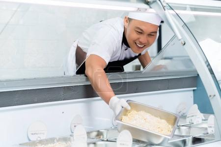 Smiling Asian chef filling a display counter