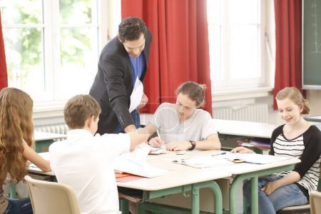 Maestro de pie mientras matemáticas lección delante de una pizarra y educa o enseña a los estudiantes o alumnos o compañeros en una escuela o clase