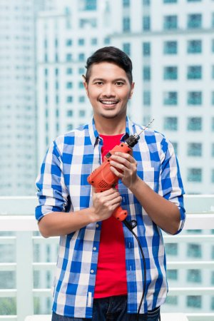 Young indonesian man with power drill, ready for home improvement