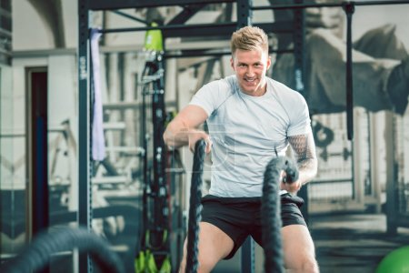 Handsome bodybuilder exercising with battle ropes during functional training