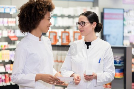 Two pharmacists analyzing the package of a new pharmaceutical drug