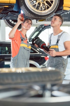 Experienced female auto mechanic with colleague at repair shop