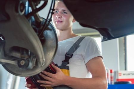 Photo pour Vue basse-angle d'un mécanicien dédié travaillant dur à la modification d'une voiture dans un atelier de réparation automobile moderne avec des services d'accordage professionnels - image libre de droit