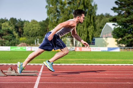 Athlete on cinder track of sports facility starts to sprint