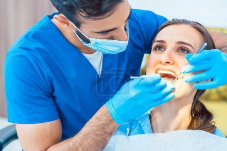 Photo pour Jeune et belle femme regardant avec confiance son dentiste fiable pendant un traitement dentaire sûr et indolore dans une clinique moderne - image libre de droit