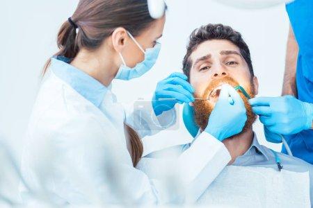 Photo pour Portrait d'un jeune homme regardant une caméra avec une expression faciale détendue, lors d'une procédure orale indolore dans le cabinet dentaire moderne d'un dentiste expérimenté - image libre de droit