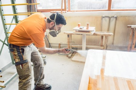 carpenter man spraying varnish on a table he works on