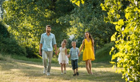 Photo for Full length view of a happy family with two children wearing casual summer clothes while holding hands during recreational walk in the park - Royalty Free Image