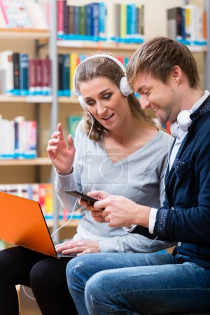 Woman and man with laptop and phone in library reading and listening