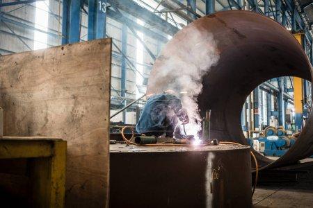 Photo pour Soudage des cols bleus à l'intérieur d'une usine fabriquant des chaudières industrielles - image libre de droit