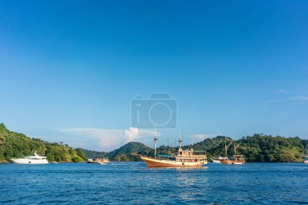 Photo for Idyllic seascape with sailing boats moored along the shore in a sunny day of summer in Flores Island, Indonesia - Royalty Free Image