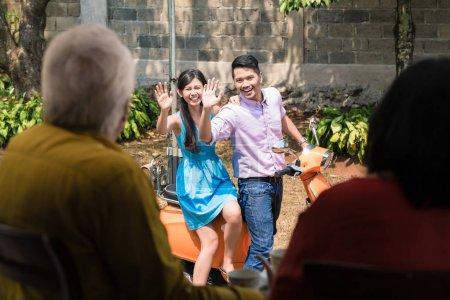 Photo pour Gai jeune homme et une femme agitant au revoir à leurs parents âgés après leur rend visite à la maison - image libre de droit
