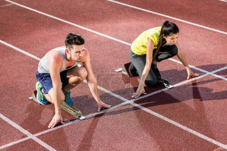 Photo for Male and female athlete in starting position at starting block of cinder track - Royalty Free Image