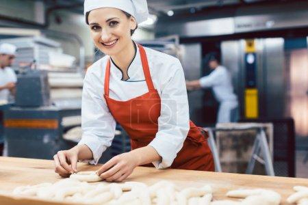 Photo pour Baker femme formant bretzels et pain, plan moyen - image libre de droit