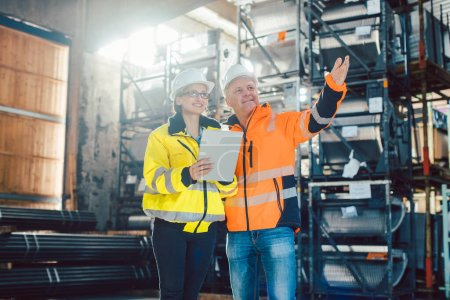 Foto de Trabajador y cliente discutiendo negocios en centro logístico o almacén - Imagen libre de derechos