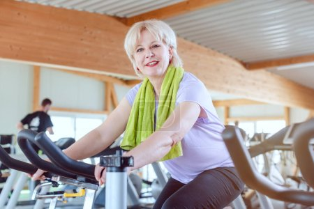 Photo for Senior woman exercising for better fitness on a bike in a modern gym - Royalty Free Image