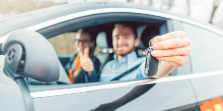 Photo for Student of driving school having passed his final test showing the car keys out of window - Royalty Free Image