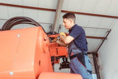 Photo pour Technicien effectuant des travaux d'entretien sur une énorme machine agricole - image libre de droit