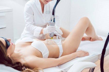 Photo pour Thérapeute utilisant la technologie laser indolore pour l'épilation dans la zone bikini d'une cliente dans un salon de beauté moderne - image libre de droit