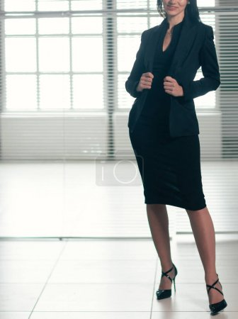 Happy young businesswoman standing in a spacious o...