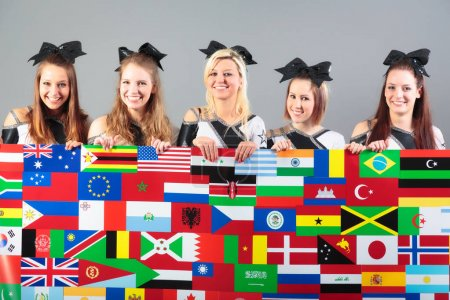 Group of cheerleaders holding poster with flags. f...