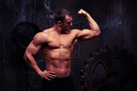 Shirtless man flexing muscles showing great relief of his arms a