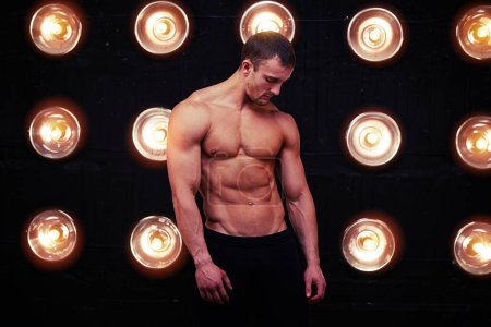 Ripped, muscular and lean body of male model in studio lights