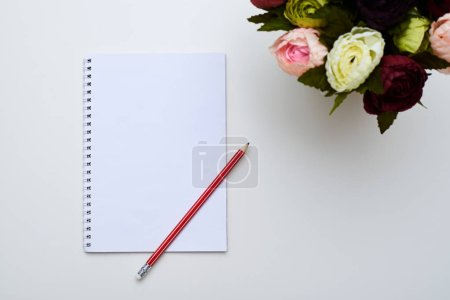 A white jotter and a red pencil next to peonies