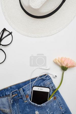 Photo pour Coup de tête de chapeau de paille, jeans en denim déchiré avec des lunettes. Vêtements et accessoires féminins placés sur fond blanc - image libre de droit