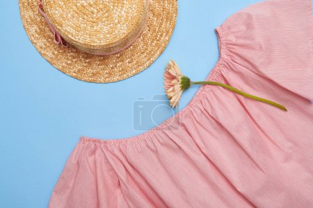 Flat lay of stylish pink blouse and straw hat