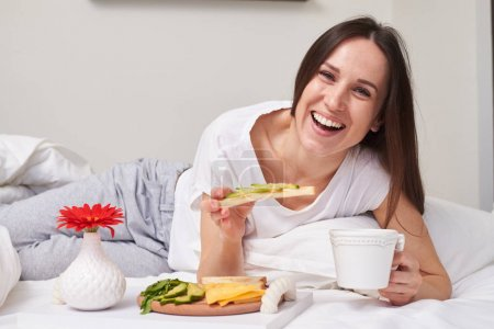 Woman eating sandwich with avocado in bed