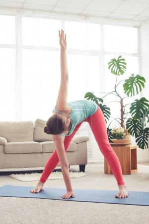 Beautiful woman doing yoga exercise on yoga mate in living room