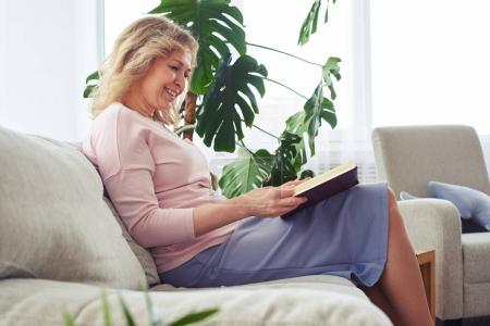 Graceful adult woman smiling while reading book