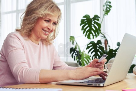 Joyful female smiling while working in laptop