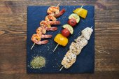 Shrimp, tomatoes, yellow peppers, zucchini and chicken on skewer