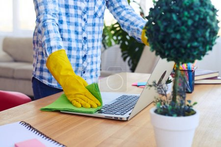 Woman in yellow gloves dusting laptop