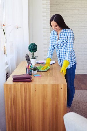 Photo for Mid shot of attractive female dusting laptop standing on table - Royalty Free Image